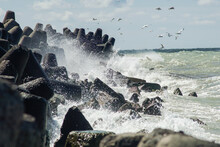 Waves Crashing On A Beach And Seagulls Flying Over