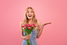Excited Blonde Woman With Tulips Celebrating Spring Holiday, Holding Something On Pink Background, Mockup For Product