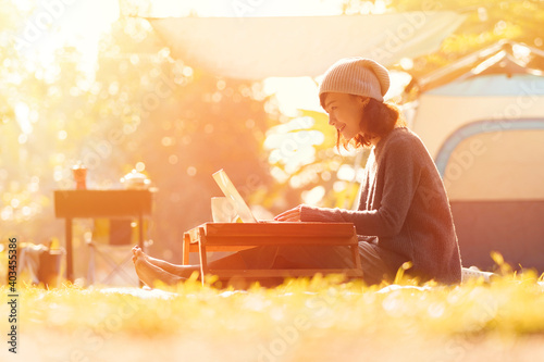 Leinwand Poster Young girl using laptop in camping tent, hiking in autumn forest