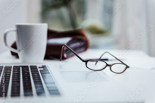 Foto Arbeitsplatz mit Laptop Kaffeetasse und Brille