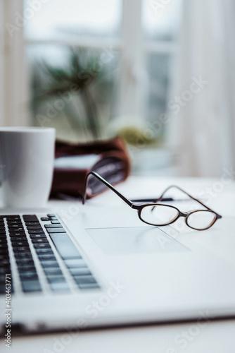 Leinwand Poster Arbeitsplatz mit Laptop Kaffeetasse und Brille