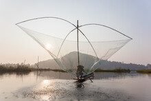 Fisherman On His Boat Moving Arched Swing Nets Above The Water At  Loktak Lake