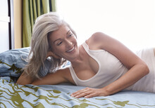 Portrait, Attractive Vivacious Mature Caucasian Woman With Silver Hair, Lying On Her Bed.