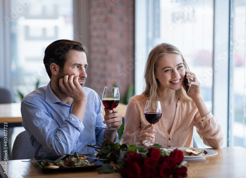 Papel de parede Millennial lady talking on cellphone during boring date, young guy feeling negle