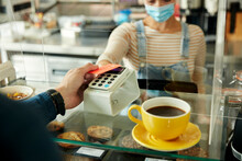 Woman In A Face Mask Holding Contactless Payment Terminal, Client Paying With Credit Card