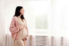 Young Beautiful Woman On Second Trimester Of Pregnancy. Close Up Of Pregnant Female In Pink Oversized Knitted Sweater With Arms On Her Round Belly. Expecting A Child Concept. Background, Copy Space.