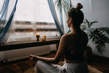 Self-care, Self-compassion, Mental Wellbeing In Post-pandemic World. Mental Health, Wellbeing, Meditation To Eliminate Anxiety. Young Woman Sitting On Floor Do Yoga Exercise And Meditation At Home