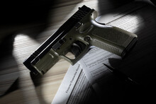 Handgun Resting On The Public Domain Forms Used For Background Checks For A Gun Purchase