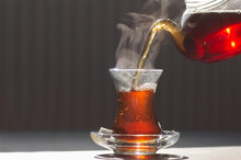 Glass Cup Of Brewed Black Turkish Tea Pouring From Teapot, Traditional Hot Drink Concept