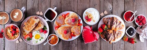 Fototapeta Valentines or Mothers Day brunch table scene. Overhead view on a dark wood banner background. Heart shaped pancakes, eggs and a variety of love themed food. obraz