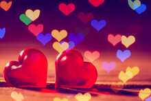 Red Little Decorative Hearts On Wooden Background With Hearts Bokeh Lights. Love Or Romantic Valentine Day Concept.