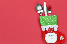 Cutlery Set And Red Santa Claus Socks On Red Paper Background And Have Copy Space.