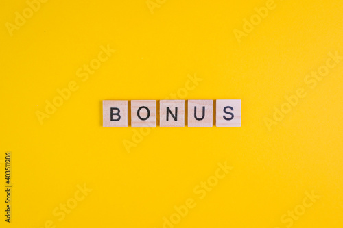 Word Bonus formed by wooden letters on orange background. Top view. Copy space