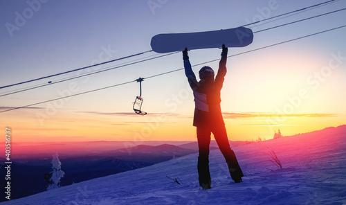 Fototapeta Silhouette of snowboarder against setting sun in lift ski resort obraz