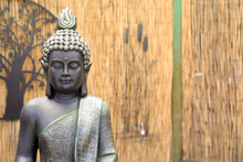 Closeup Of Statue Of Buddha With Bamboo Background