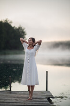 Young Woman Standing On A Wooden Pier And Breathe Deeply On Chilly Morning With A Mist Over Water.