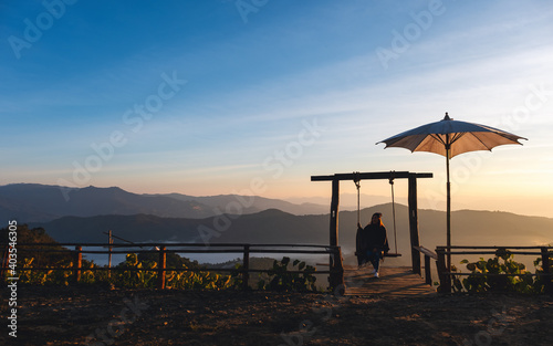 Obraz A female traveler sitting on a swing while watching a beautiful view and sunrise in the morning - fototapety do salonu