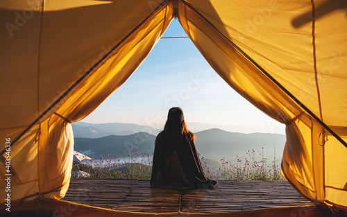Obraz Rear view image of a woman sitting on wooden balcony while watching a beautiful mountains and nature view outside the tent - fototapety do salonu