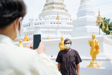 Asian Senior Elderly Couple Wear Mask Taking Photo With Smartphone In Thai Temple.
