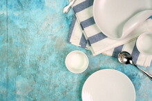 White Empty Ceramic Plates On Grainy Texture Blue Background With Stripes Napkin, Bowl And Silver Spoon As Serving Food Preparation Concept. Top View Of White Tableware
