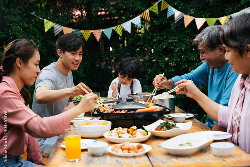 Asian family enjoy eating BBQ together outdoor at park. Fototapete