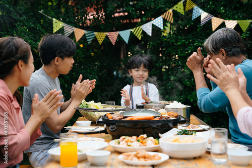 Valokuvatapetti Family clap a hands and sing happy birthday song in dining party outdoor