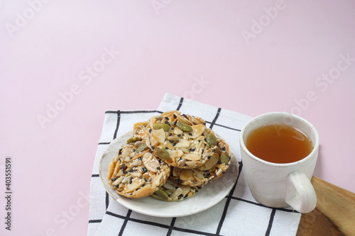 Fotografiet A cup of tea and a plate of Florentine cookies on square napkin in wooden board