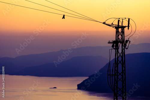 Fotografie, Obraz High voltage towers on coast at sunset