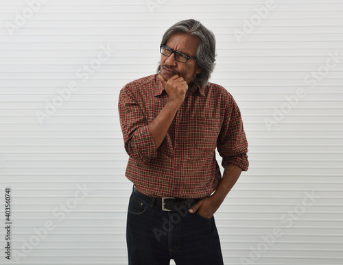 Fototapeta Thoughtful senior businessman in red casual shirt, blue jeans and eyeglasses standing over white wall background, Funny face expression pose obraz