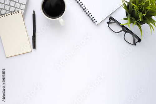 Fototapeta Top view above of White office desk table with keyboard, notebook and coffee cup with equipment other office supplies. Business and finance concept. Workplace, Flat lay with blank copy space. obraz na płótnie