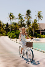 Woman Riding Bicycle At A Tropical Beach Resort
