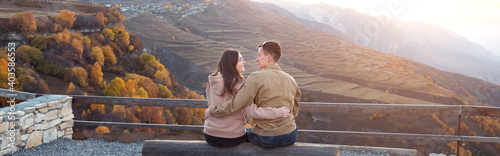 Photo Romantic couple in love kisses and hugs sitting on large log of observation deck
