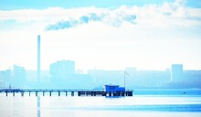 Seascape Of A Pier Against A Cityscape With A Factory Pipe In The Background. Atmospheric Landscape. Nature, Ecology, Ecological Issues, Environmental Damage. Panoramic View
