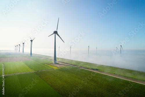 Photo Offshore wind turbines standing in fog on the IJsselmeer inland sea, land based