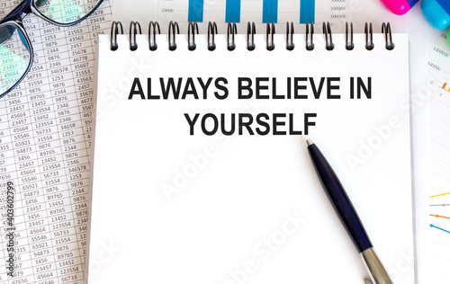 Canvas Print In the notebook, the text ALWAYS BELIEVE IN YOURSELF, next to the pen, glasses, background are graphs and reports