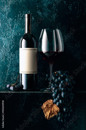 Obraz Red wine and blue grapes with dried up vine leaves on an old dark blue background. - fototapety do salonu