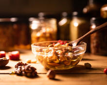 Farmer Honey Mixed With Nuts, Seeds In A Transparent Plate With A Wooden Spoon, Jars, Walnuts, Dried Apricots And A Branch Of Red Rowan On A Rustic Wooden Kitchen Table. Still Life Photography