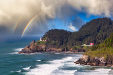 Lighthouse On Top Of The Rocky Shore Of Pacific Ocean. Taken On The Scenic Route In Oregon Coast, USA. Colorful Sunset Sky With Rainbow Art Render.