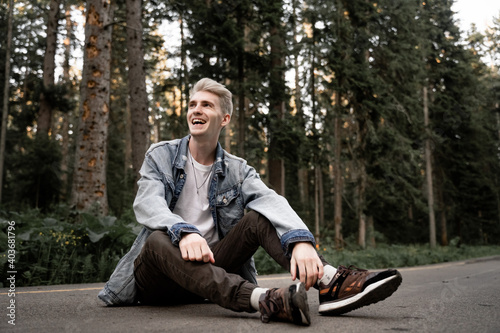 Fototapeta an unusual young guy with gray hair sits on the ground and laughs out loud