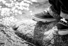 Black And White Image Of A Youths Feet Standing On A Rock With A Peaceful River Going Past.