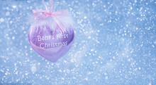 Christmas Toy In The Form Of A Pink Heart With Feathers And Lettering Baby's First Christmas On A Glittery Silver Background