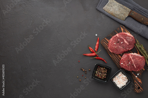 Fototapeta Beef steaks on cutting board and spices on black slate background. Top view. Steak menu obraz