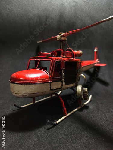 Fotografia Red and white retro style metal helicopter on a black background.