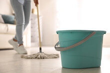 Plastic Bucket And Woman Mopping Floor In Living Room, Closeup. Cleaning Supplies