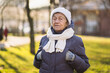 canvas print picture - Portrait Caucasian senior woman with gray hair and deep wrinkles 90 years old posing in warm clothes, white knitted scarf and hat in park, sunny frosty weather. Active old age, walking elderly female