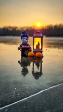 A Fluffy Toy, A Cup And Two Oranges On A Frozen Sea At Sunset