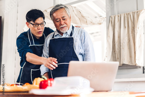 Fototapeta Portrait of happy love asian family senior mature father and young adult son having fun cooking together and looking for recipe on Internet with laptop computer to prepare the yummy eating lunch  obraz