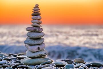 balanced stone pyramid landscape on pebble sea beach at dawn. Polished stone figure against stormy ocean background. Sunrise on seashore. Sunset on beach. Orange sky and sea water on morning