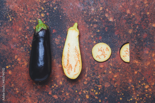 Fototapeta Fresh and sliced eggplants on grunge background