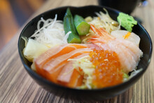 Fresh Raw Seafood Mixed Rice Bowl. Japanese Rice With Sashimi Of Salmon, Scallop, Okra And Ikura (Salmon Eggs) On A Wooden Table.